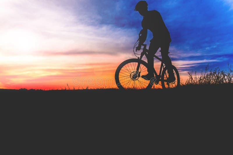 站立与在小山足迹的登山车的骑自行车者在日落 免版税库存图片