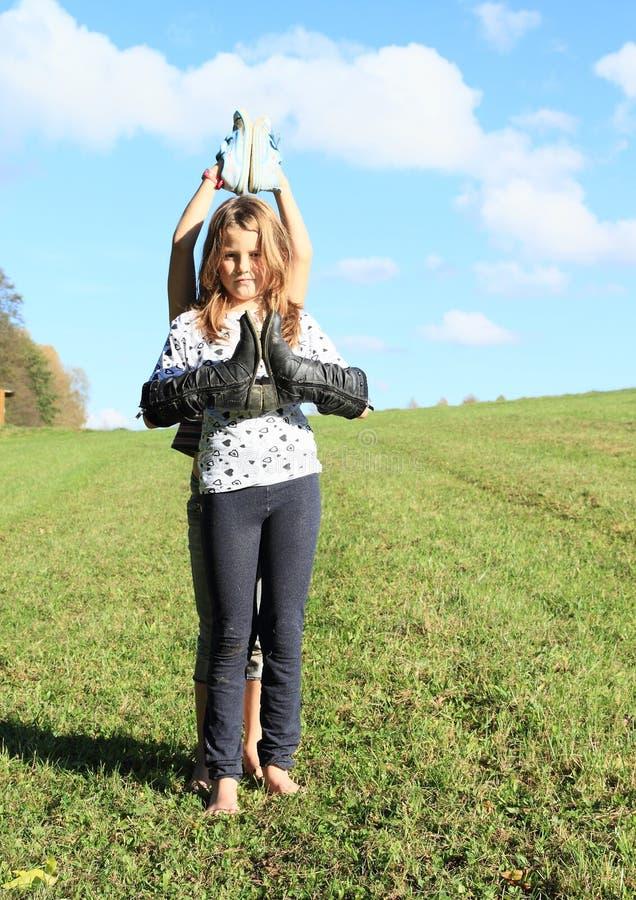 站立与在手上的起动的女孩 免版税图库摄影
