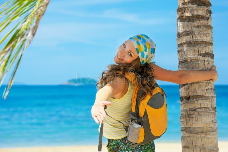 站立与在海岸海和looki的背包的少妇微笑 库存照片