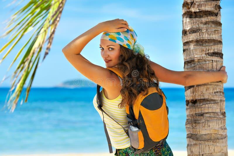 站立与在海岸海和lookin的背包的愉快的少妇 库存图片