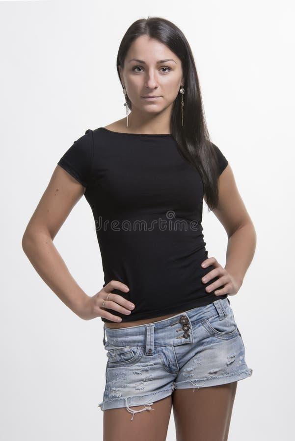 牛仔布短裤的美丽的深色的妇女 库存图片