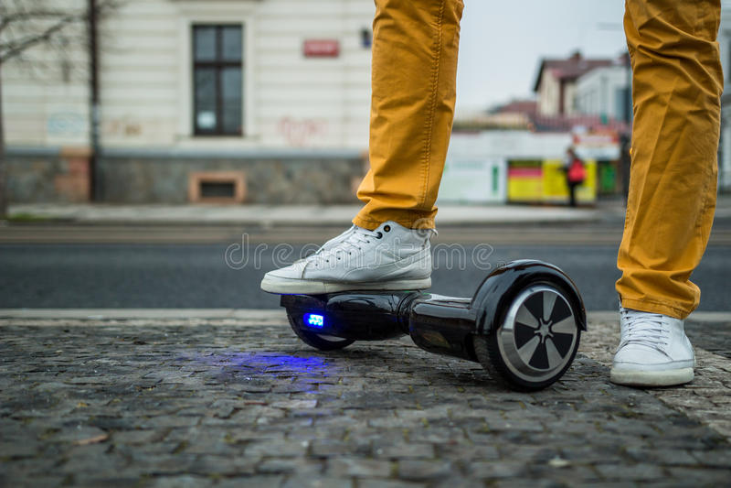 站立与在街道上的hoverboard的人 库存照片
