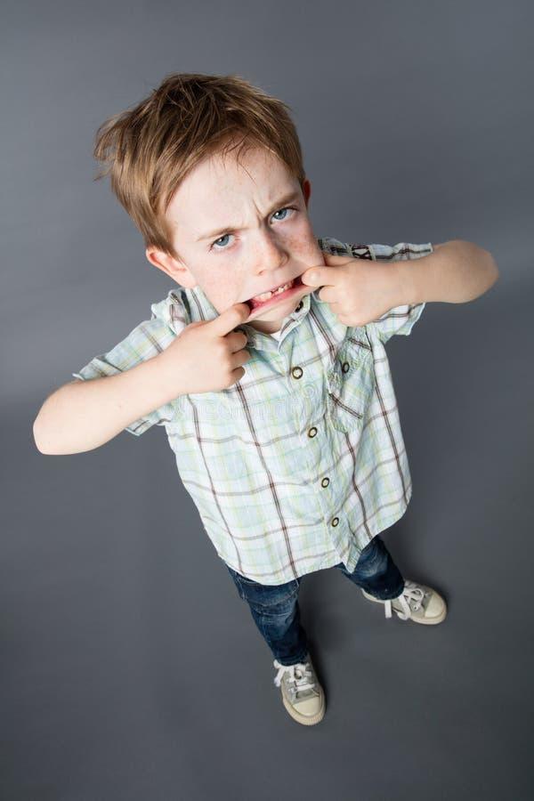 站立与坚定的态度的大嘴的不快乐的年轻男孩 库存图片