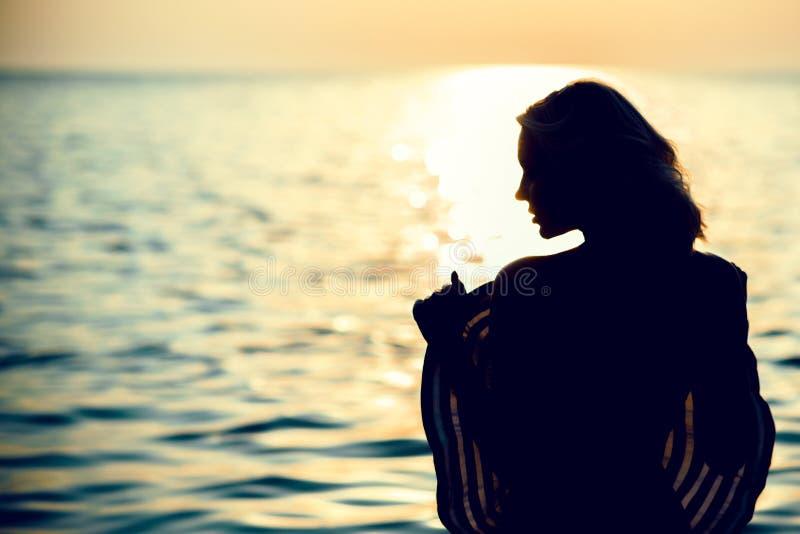站立与她的一名美丽的妇女的剪影回到在海水的照相机在拿着一个大宽充满的帽子的日出 库存照片