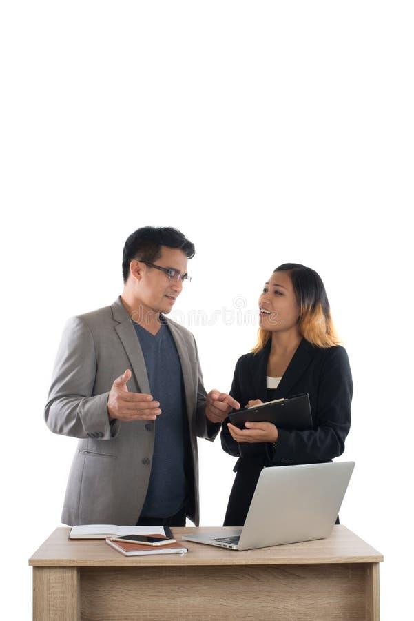 站立与她的关于t的上司交谈的年轻女商人 库存照片