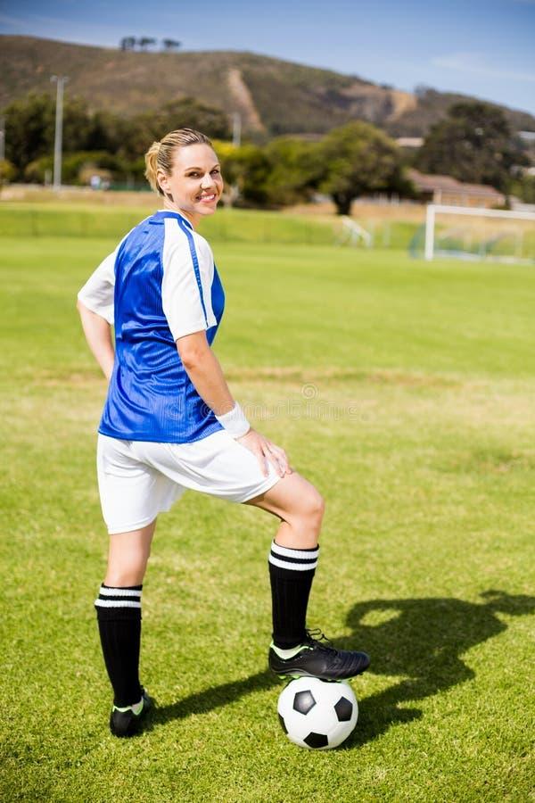 站立与她的在球的脚的女性足球运动员画象  免版税库存图片