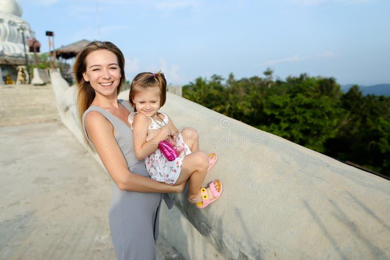 站立与小女儿的年轻俏丽的母亲在普吉岛 库存照片