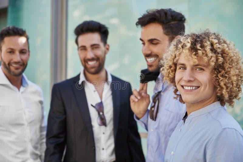 站立与工友微笑的年轻愉快的商人 库存图片