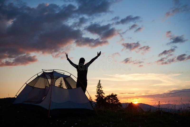 站立与开放胳膊的妇女后面看法剪影临近帐篷在山顶部 库存图片