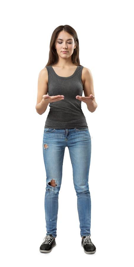 站立与手肘的年轻女人和蓝色牛仔裤正面图灰色上面的弯曲,好象拿着无形的片剂被隔绝 库存照片