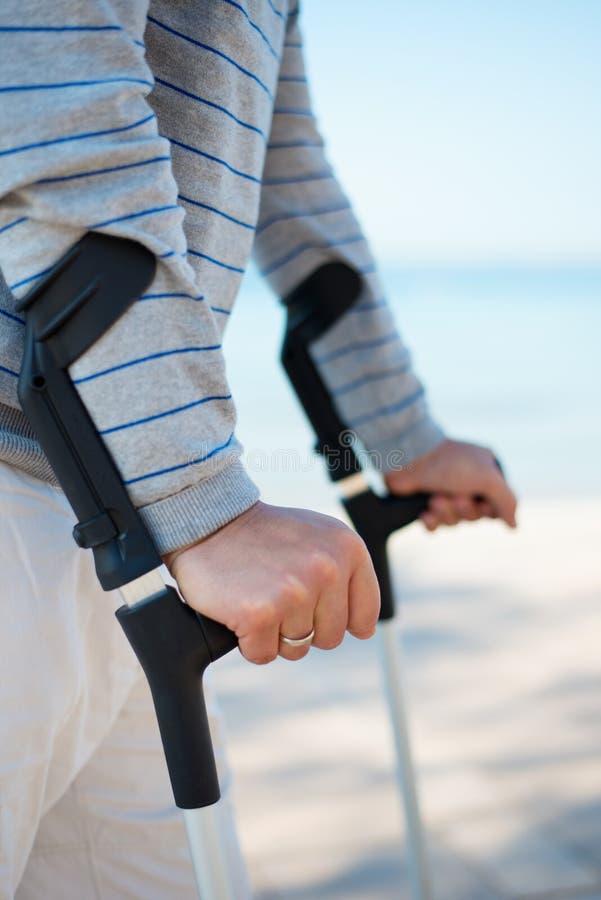站立与拐杖的受伤的人 库存照片