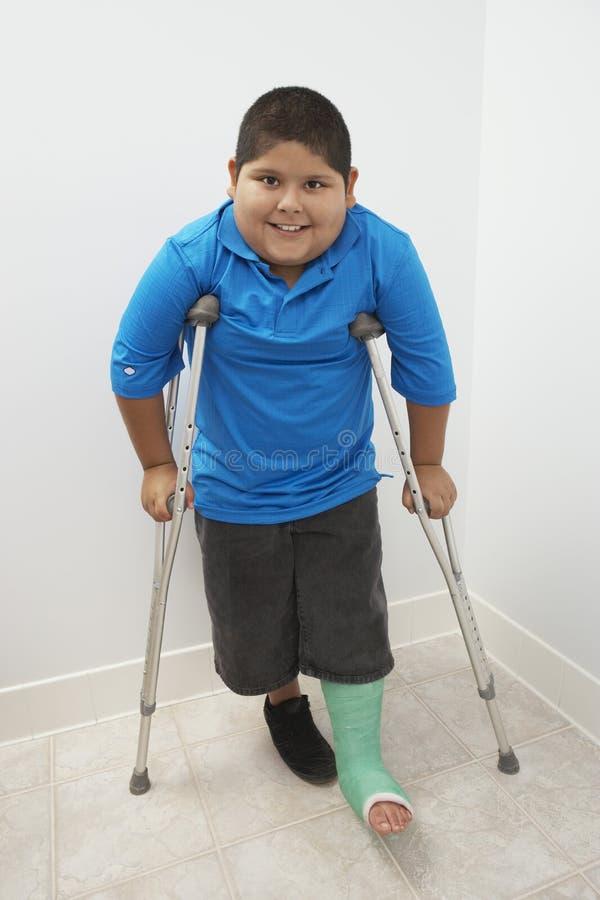 站立与拐杖的男孩 库存照片