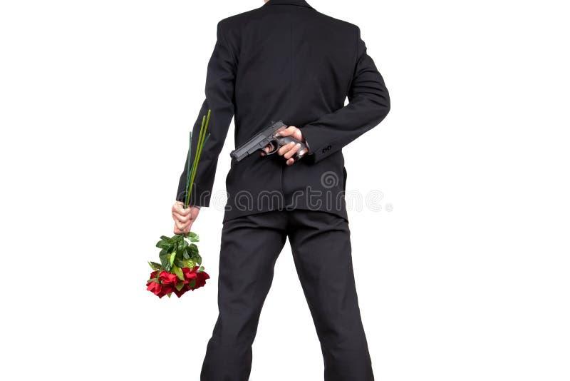 站立与拿着罗斯花花束和掩藏的亚洲商人在他的后的枪  库存图片