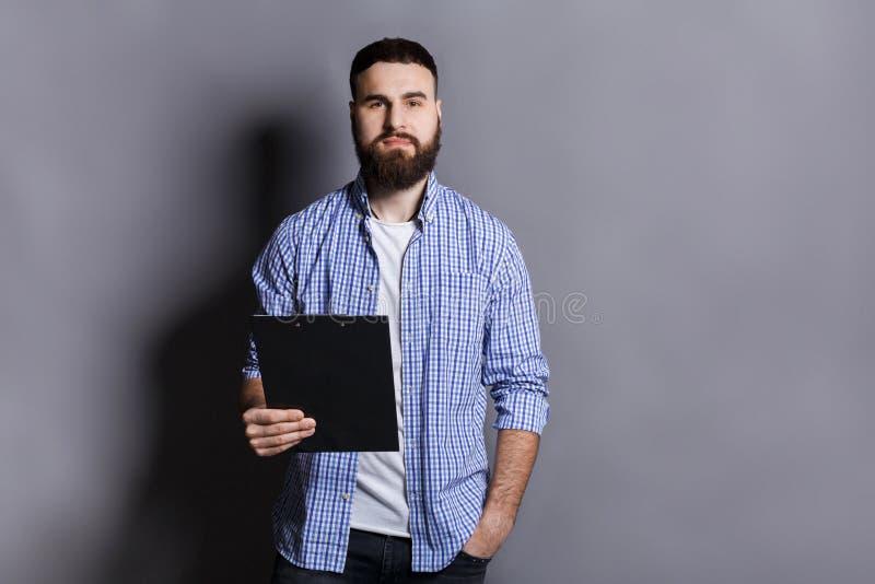 站立与文件夹的年轻严肃的有胡子的人 库存图片