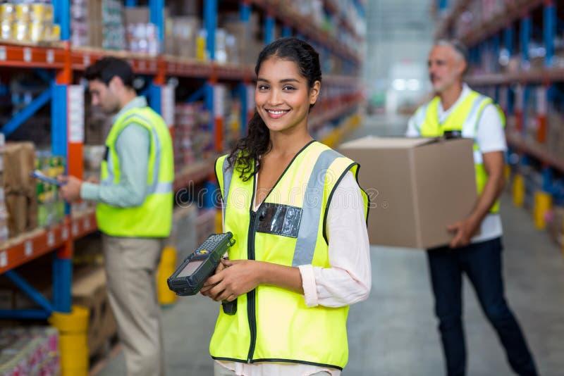站立与条形码扫描器的女性仓库工作者画象  免版税库存图片