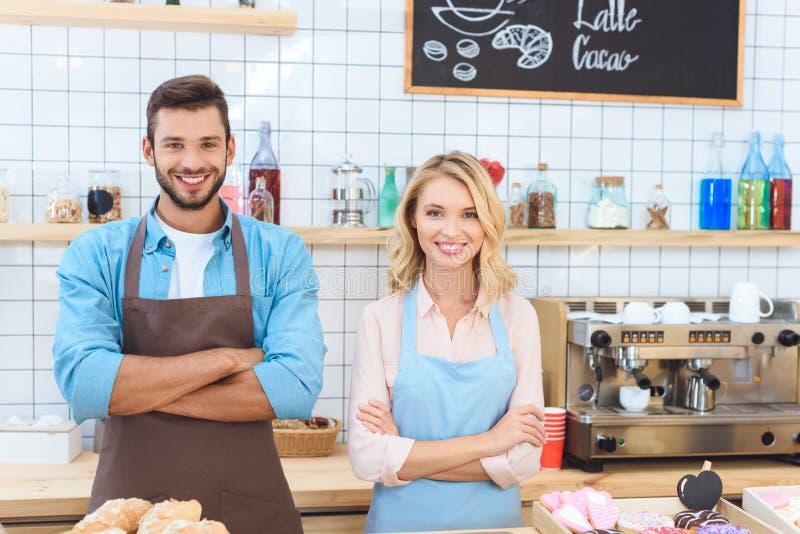 站立与横渡的胳膊和微笑的确信的年轻咖啡馆工作者 库存照片