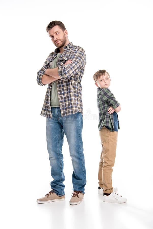站立与横渡的胳膊的全长观点的严肃的父亲和儿子 库存图片