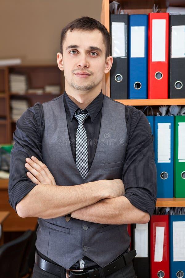站立与横穿的年轻经理画象在机架附近武装用文件文件夹 免版税库存照片