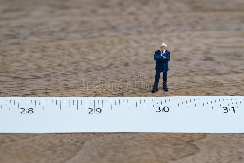 站立与测量的磁带的微型商人在第30 库存照片