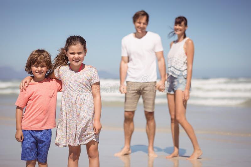 站立与父母的微笑的兄弟姐妹画象在背景中 库存照片