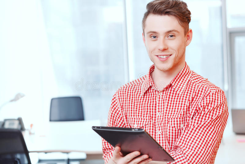 站立与片剂的微笑的办公室经理 库存图片
