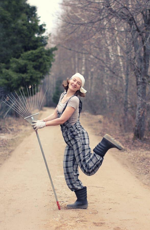 站立与犁耙的花匠或农夫妇女 秋天或春天wo 免版税库存照片