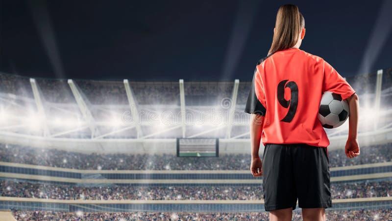 站立与球的女性足球运动员反对拥挤体育场在晚上 库存图片