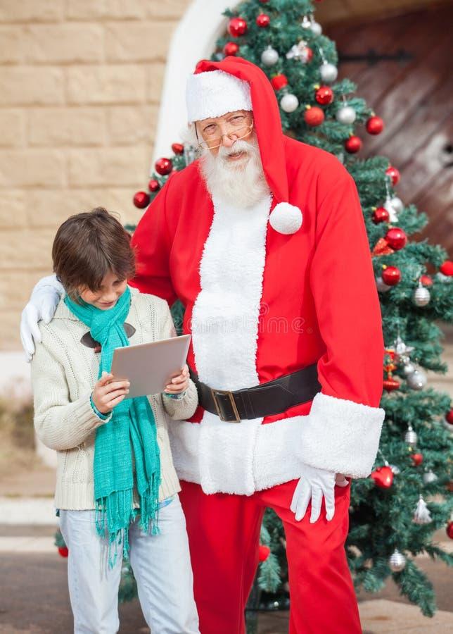 站立与男孩的圣诞老人使用数字式片剂 库存图片
