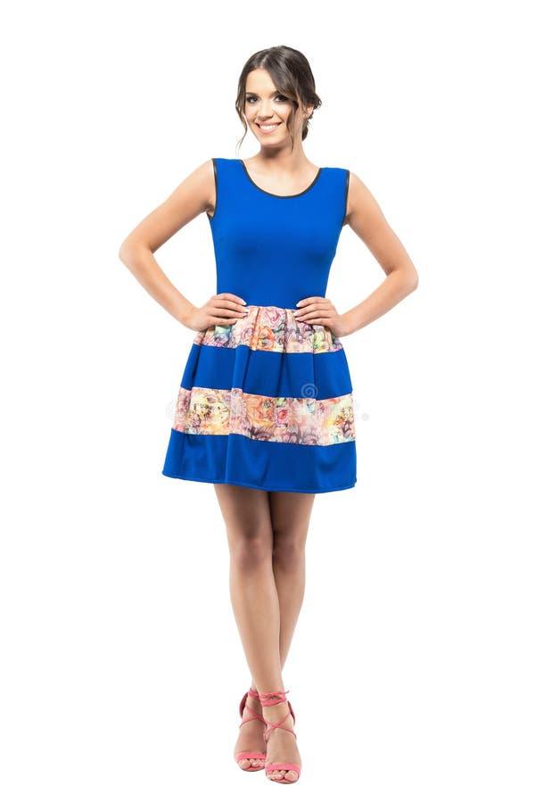 站立与盘的腿和两手插腰的姿势的夏天蓝色礼服的华美的逗人喜爱的女孩 库存照片