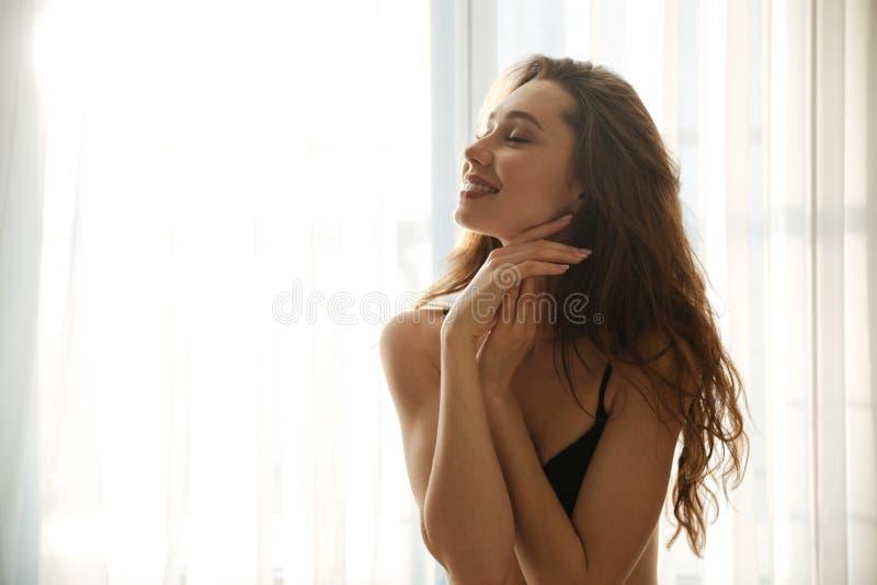 站立与眼睛的女用贴身内衣裤的微笑的肉欲的少妇关闭了 免版税库存图片