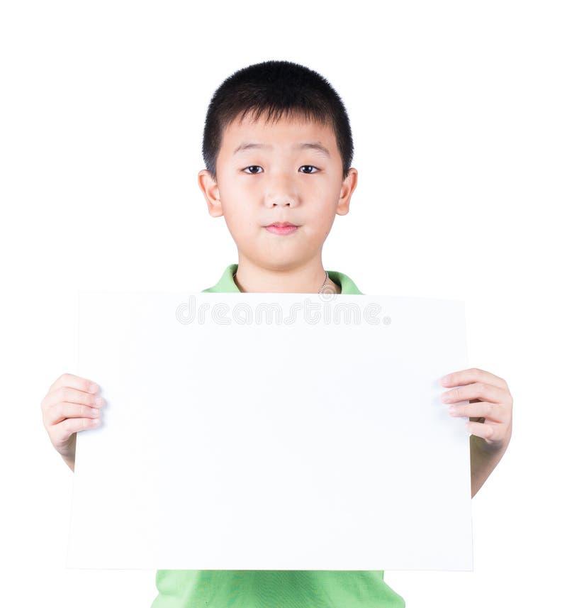站立与空的水平的白纸的微笑的男孩在白色背景隔绝的手上 库存图片