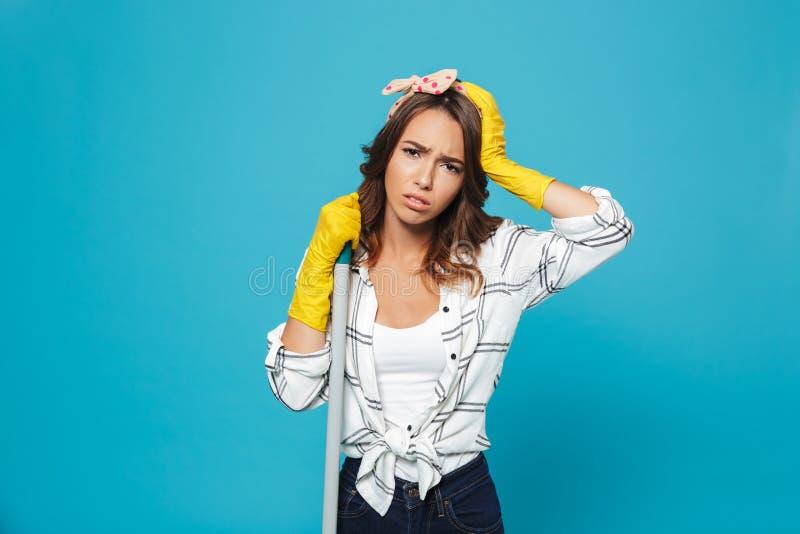 站立与笤帚的一位疲乏的主妇的画象 免版税库存图片