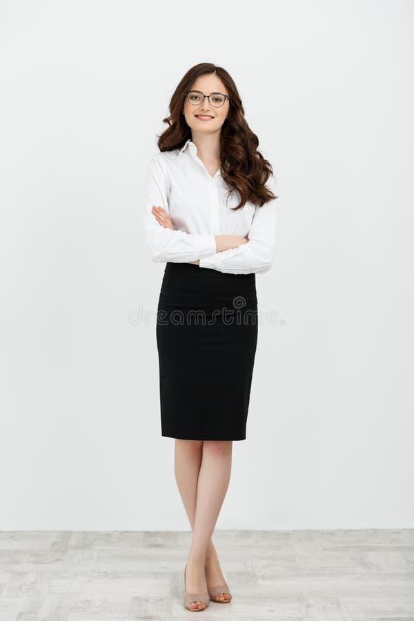 站立与胳膊的一名微笑的女实业家的全长画象在白色背景折叠了隔绝 库存照片