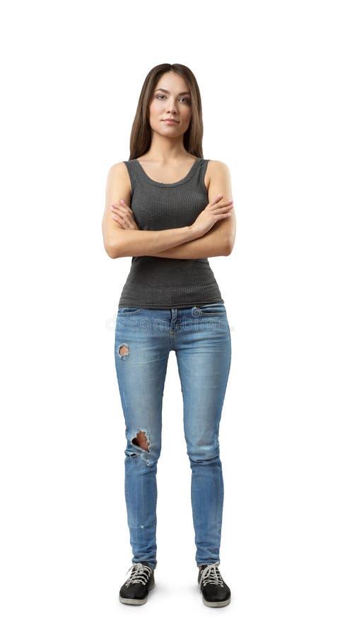 站立与胳膊的年轻可爱的妇女和蓝色牛仔裤正面图灰色无袖的上面的横渡在被隔绝的胸口 免版税库存照片