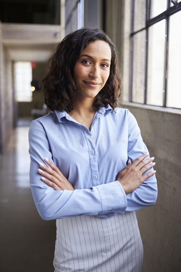 站立与胳膊的年轻混合的族种女实业家横渡 免版税库存照片