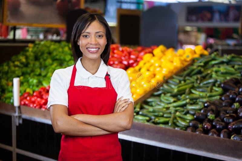 站立与胳膊的微笑的女职工在有机部分横渡了 免版税库存照片