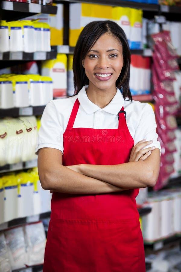 站立与胳膊的微笑的女职工在杂货部分横渡了 免版税库存图片