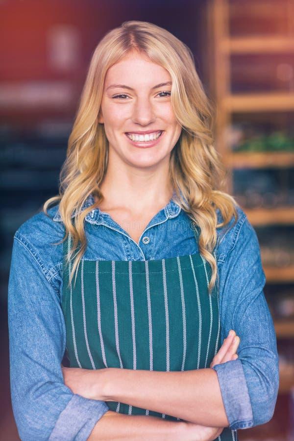 站立与胳膊的微笑的女职工在超级市场上横渡了 免版税库存照片
