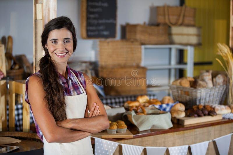 站立与胳膊的微笑的女职工画象横渡在面包店商店 免版税库存图片