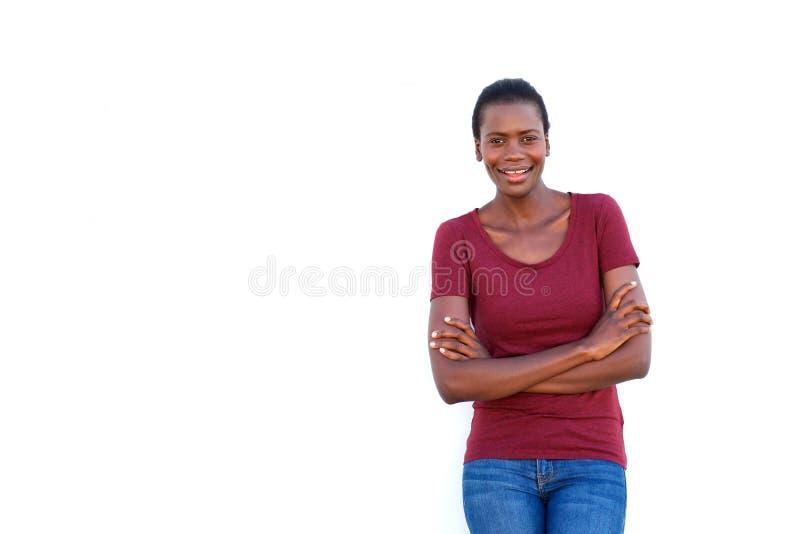 站立与胳膊的微笑的年轻黑人妇女在白色背景横渡了 库存照片