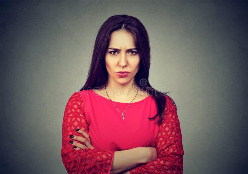 站立与胳膊的恼怒的妇女在灰色背景折叠了 免版税库存图片