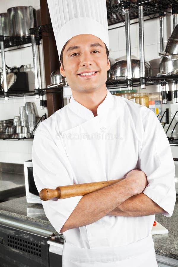 站立与胳膊的愉快的厨师横渡 免版税库存图片