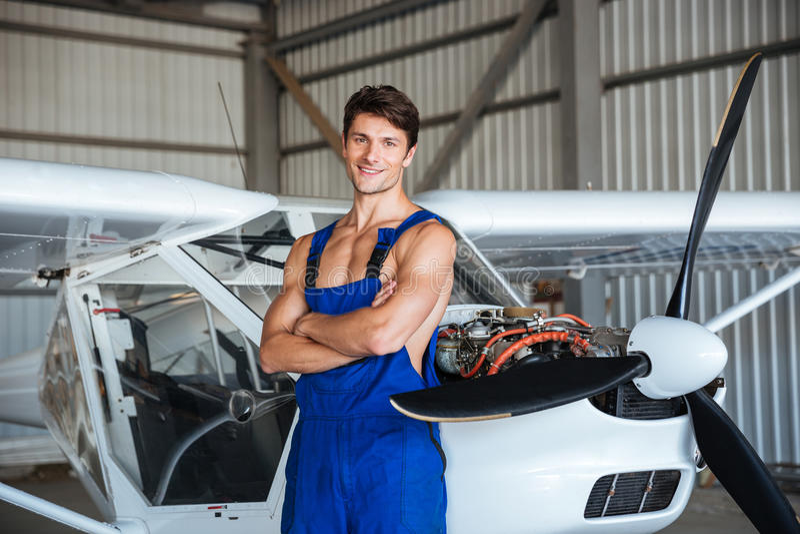 站立与胳膊的愉快的飞机机械员在小飞机附近横渡了 库存照片