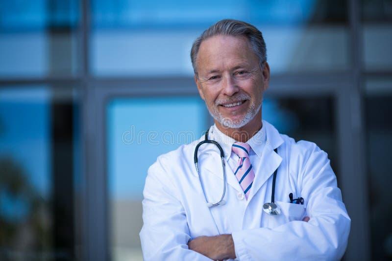 站立与胳膊的男性外科医生画象横渡 免版税库存照片