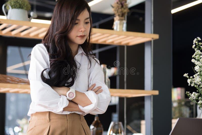 站立与胳膊的确信的女实业家在办公室横渡了 Yo 图库摄影