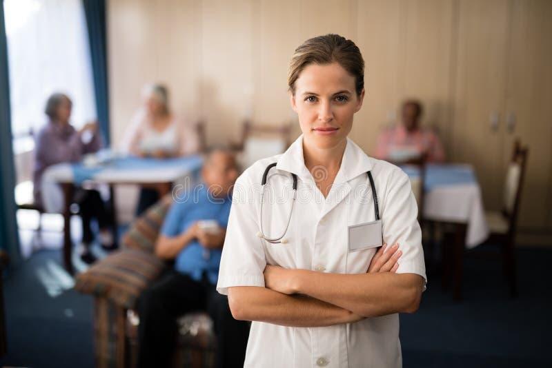 站立与胳膊的确信的女性医生画象横渡 免版税库存照片