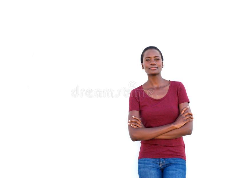 站立与胳膊的确信的年轻非洲妇女在白色背景横渡了 图库摄影
