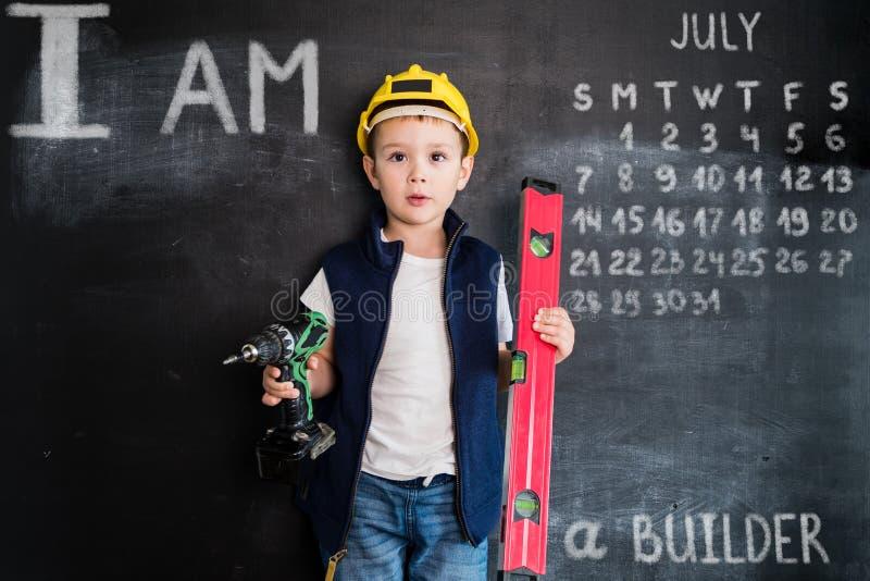 站立与螺丝刀的年轻男孩` s在黑板附近 新建造者 2019日历的创造性的设计观念 7月 库存图片