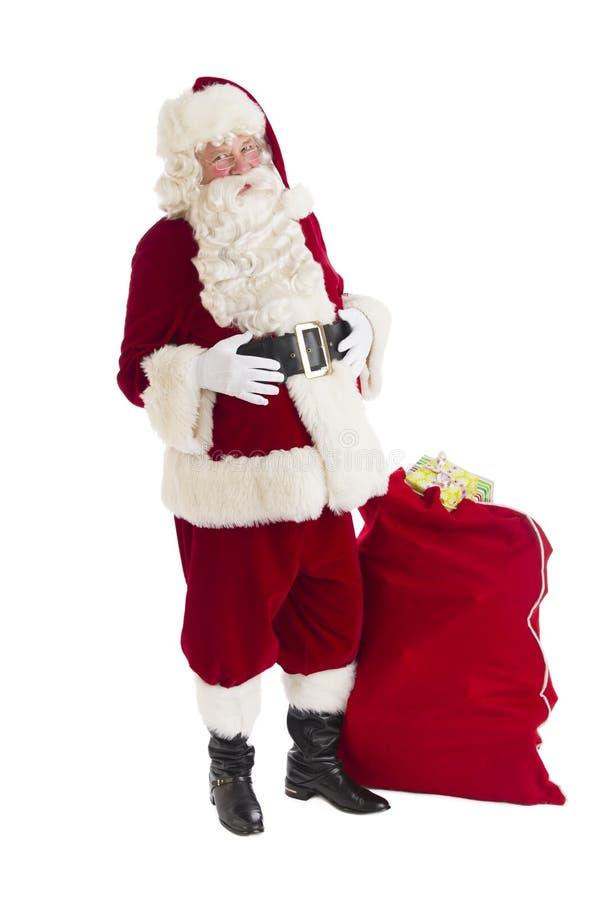 站立与袋子的圣诞老人有很多礼物 免版税库存照片