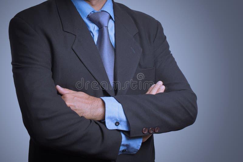 站立与被交叉的双臂的一套时髦的衣服的商人 免版税图库摄影